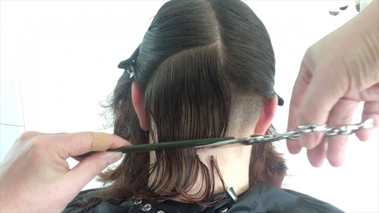 A curly bob haircut with shaved undercut nape undercut
