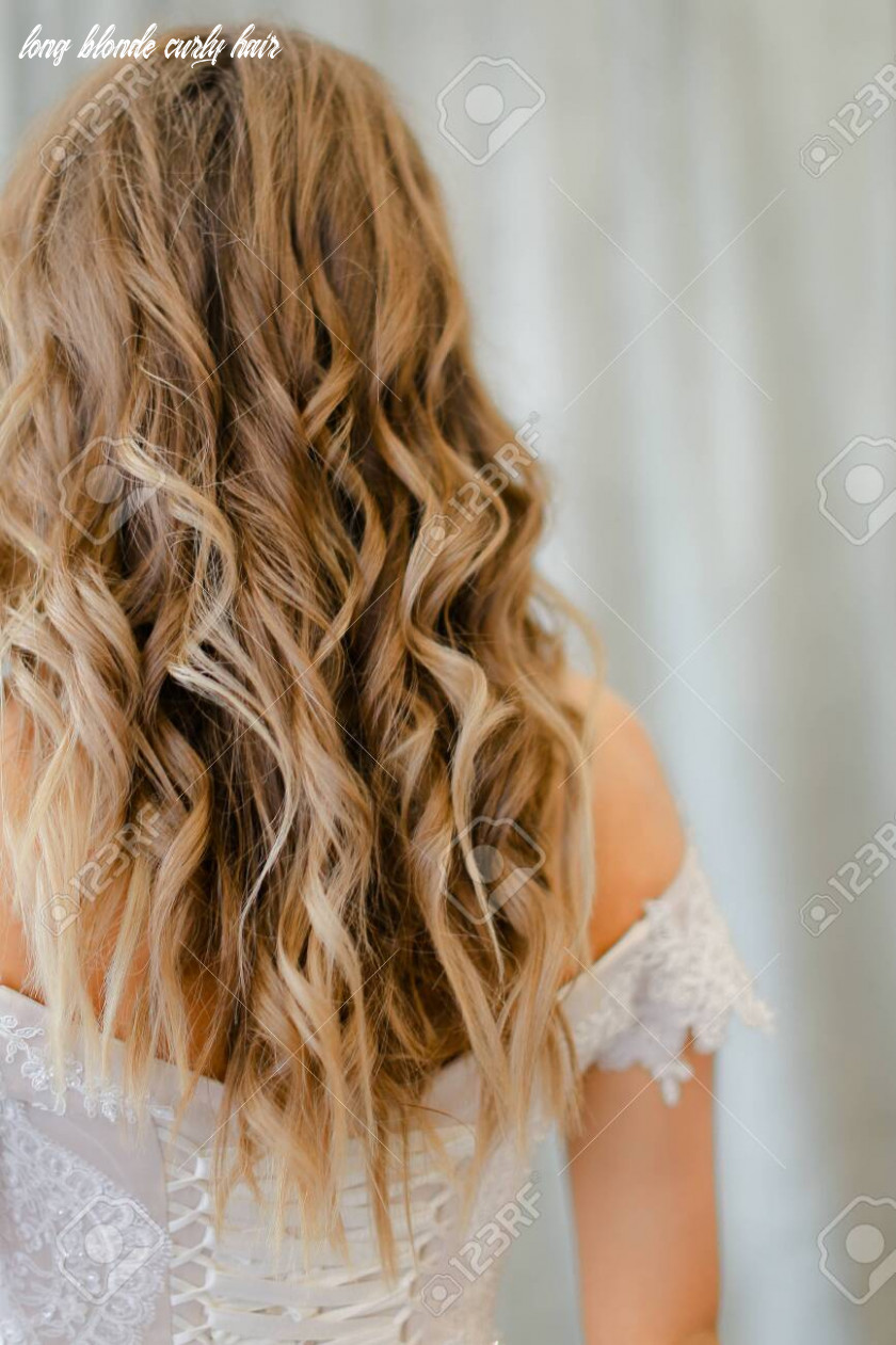 Back view of bride with long blonde curly hair at studio. Concept..