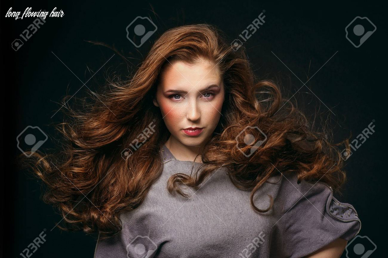 Beautiful young woman with long flowing hair on a black background long flowing hair