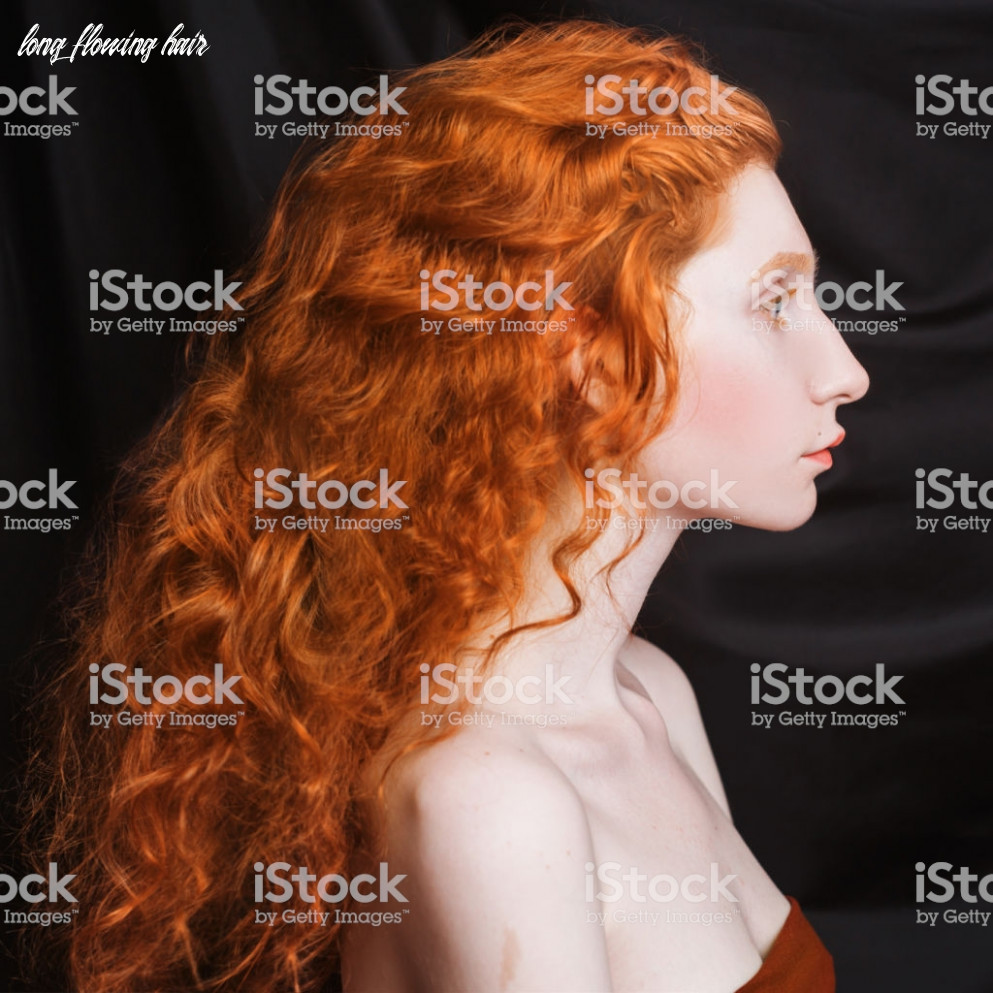 Woman with long curly red flowing hair on a black background