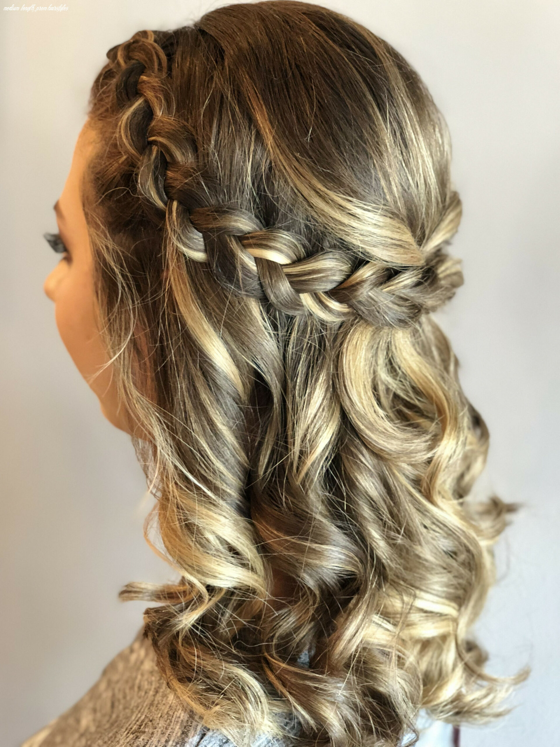 A bella bombshell half up half down with curls, braided prom hair