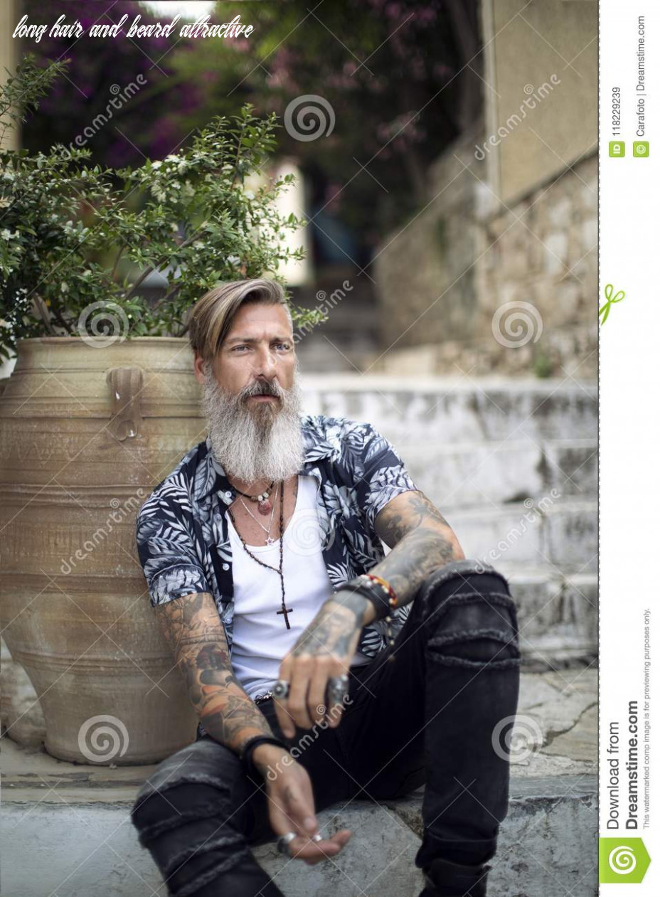 Attractive Man With A Beard And Tattoos Is Sitting On The ...