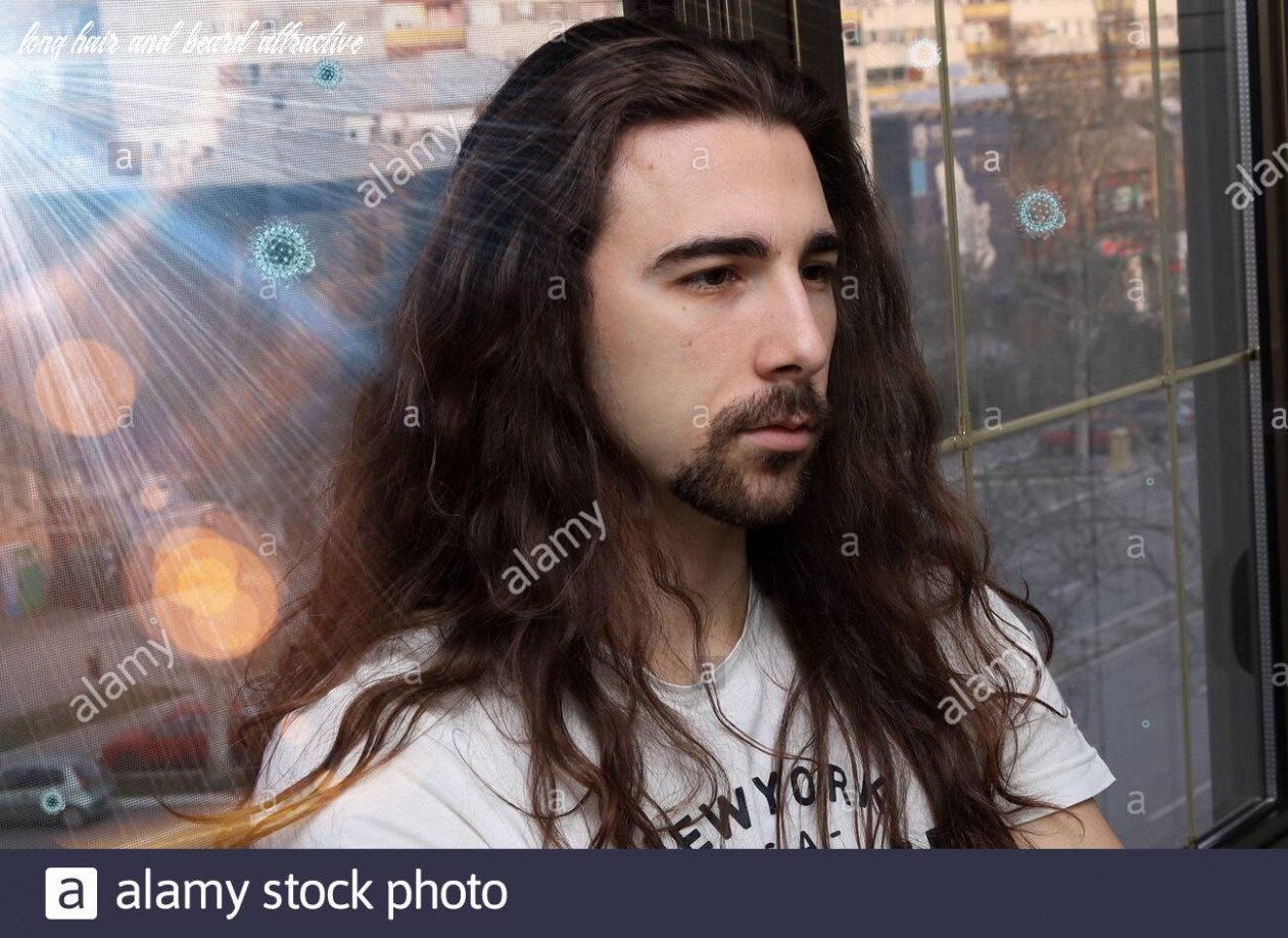 Attractive young caucasian guy with long hair and beard is