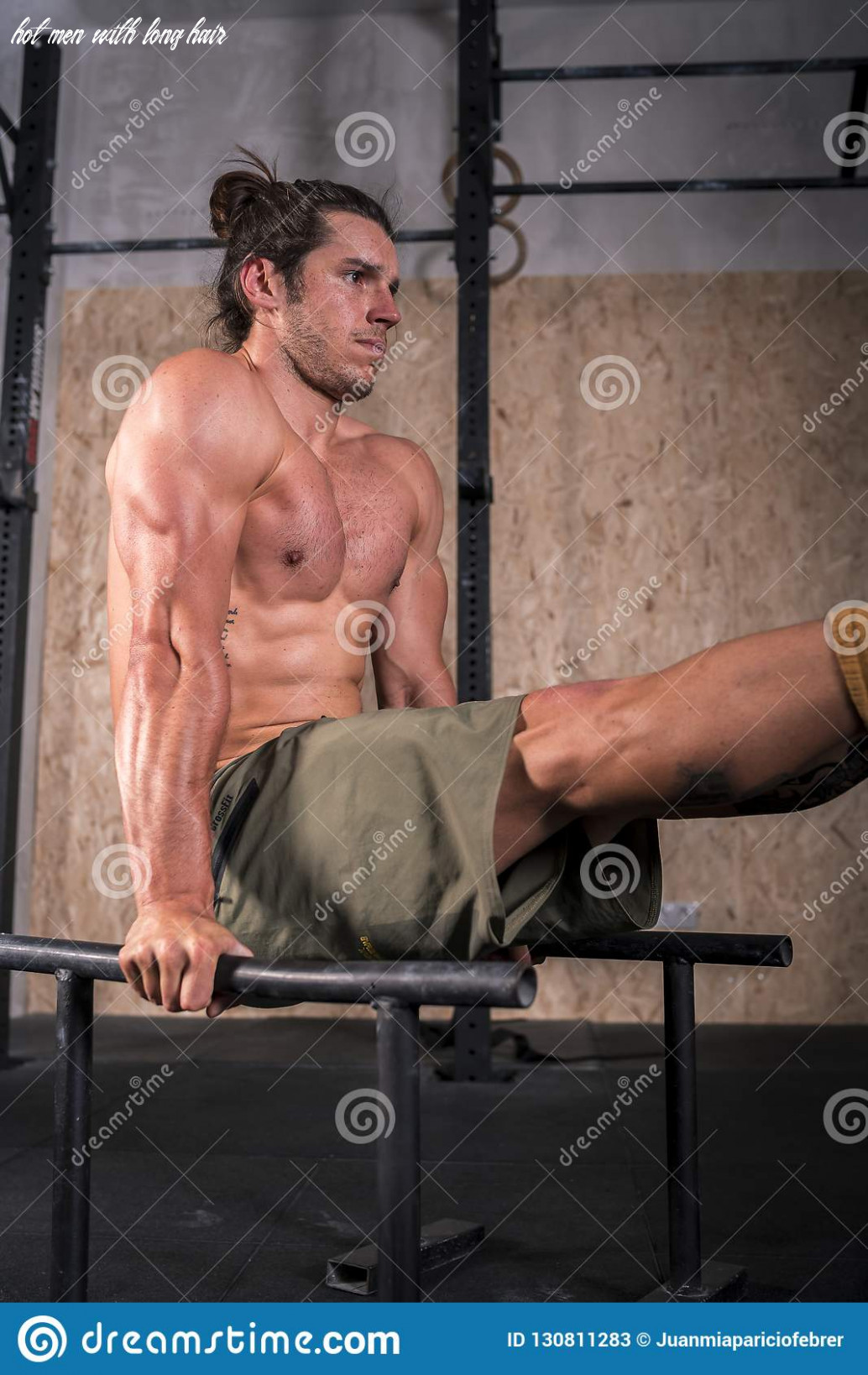 Portrait of a strong young man exercising in parallel bars stock