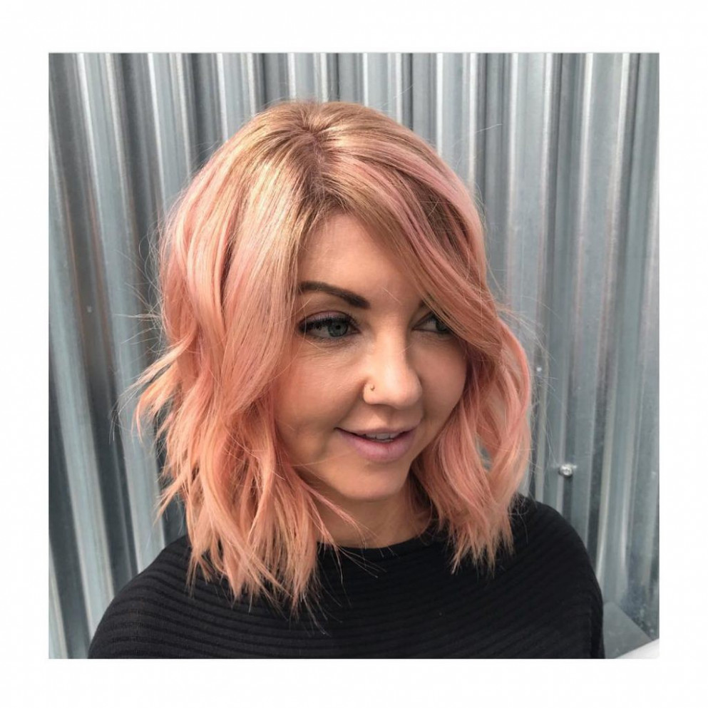 Rose gold bob with long side swept bangs and messy beach waves