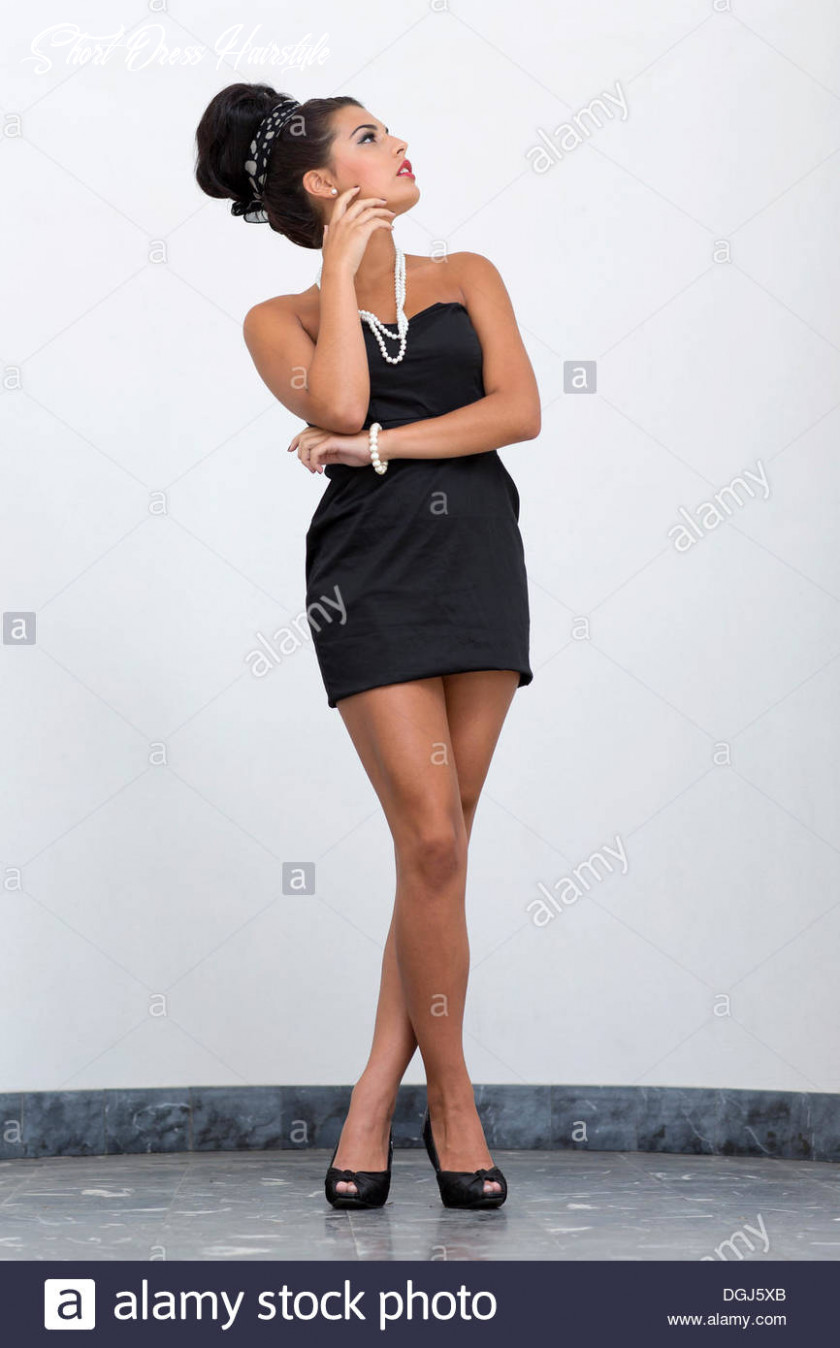 Young woman with an updo hairstyle wearing a short black dress and